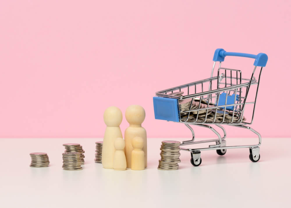 wooden-figurines-family-stacks-metallic-money-miniature-shopping-cart-white-table-family-budget-control-concept-savings