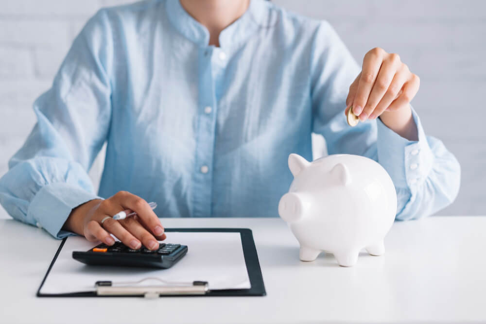 businesswoman-using-calculator-while-inserting-coin-piggybank-workplace