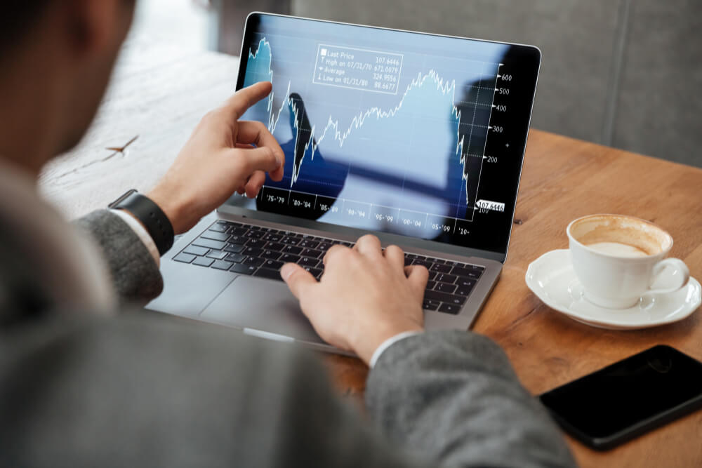 cropped-image-businessman-sitting-by-table-cafe-analyzing-indicators-laptop-computer