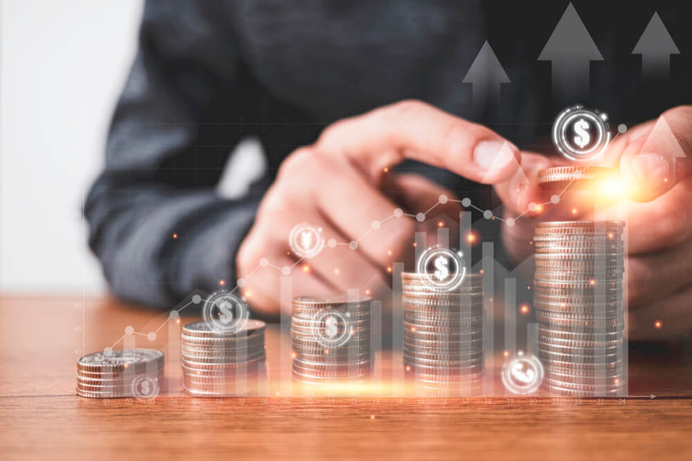 businessman-putting-coins-stacking-with-virtual-graph-currency-sign-such-as-dollar-pound-sterling-yen-yuan-euro-business-investment-saving-profit-concept