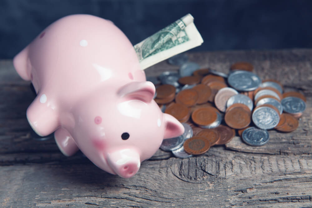 coins-piggy-bank-with-dollar-bill-table