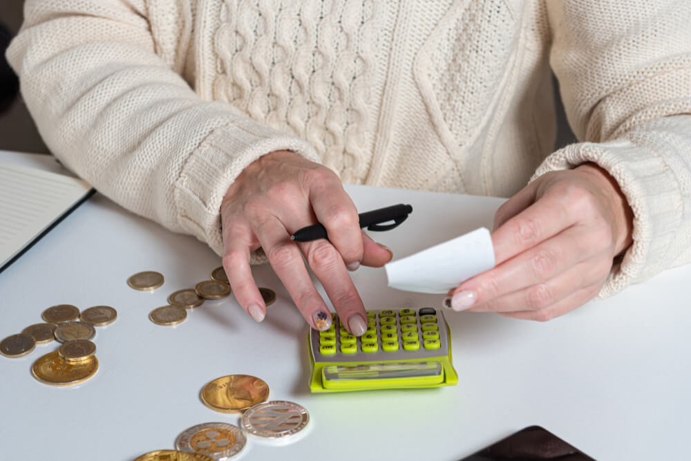 female-hands-counting-data-vat-taxes-cost-doing-paperwork-home-office-table-close-up